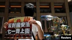 香港一名抗議者舉牌反對港版國安法,號召七一遊行。(2020年6月30日)