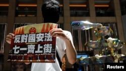 香港一名抗議者舉牌反對港版國安法,號召七一遊行。 (2020年6月30日)