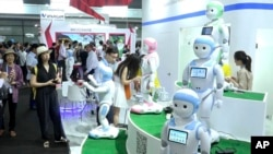 In this image taken from video, visitors look at iPal robots during the Shanghai CES electronic show in Shanghai, China, June 8, 2017. More than 50 companies are showcasing a new generation of robots at this week's Shanghai CES electronics show, most of which serve as companions at home, or butlers in shopping malls.