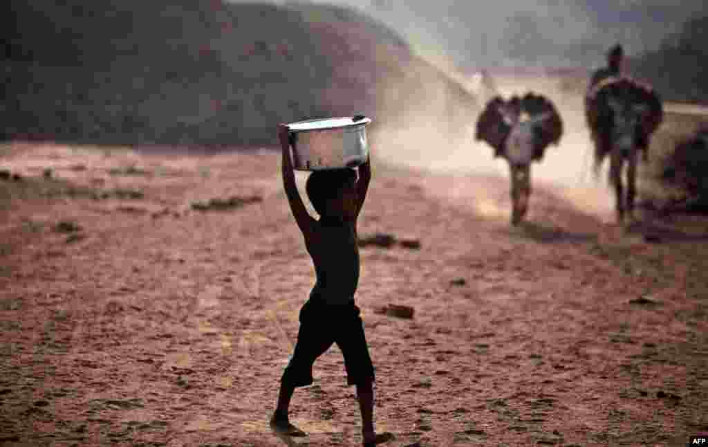 June 2: A Pakistani boy walks toward a water point to collect water for his family, on the outskirts of Islamabad, Pakistan. (AP Photo)