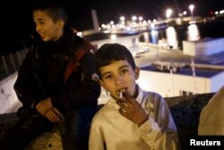 FILE - Mohamed, a Moroccan youth, smokes a cigarette near Melilla's harbor in Spain's north African enclave, Dec. 8, 2013.