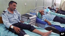 Iraqi policemen lie wounded at a hospital after a bomb blast in Hilla, south of Baghdad, May 5, 2011