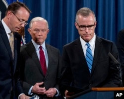 FILE - Andrew McCabe, right, accompanied by Attorney General Jeff Sessions, second from left, Deputy Attorney General Rod Rosenstein, takes the podium at a news conference at the Department of Justice, July 20, 2017, in Washington.