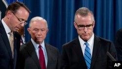 El Director Interino del FBI Andrew McCabe, a la derecha, acompañado por el Fiscal General Jeff Sessions, segundo desde la izquierda. El Vice Fiscal Rod Rosenstein, sube al podio en una conferencia de prensa en el Departamento de Justicia el 20 de julio de 2017 en Washington.