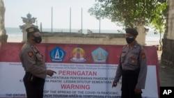 Cảnh sát Indonesia canh gác lối vào một bãi biển bị phong tỏa tại Bali.