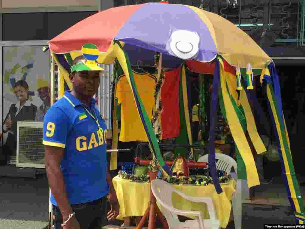 Un vendeur se promène dans les rues de Port-Gentil avant le match du groupe D, au Gabon, le 16 janvier 2017. (VOA/ Timothée Donangmaye)