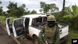 Soldiers stand guard next to a vehicle belonging to gunmen after a shootout in the municipality of Tacambaro near Morelia August 16, 2011.