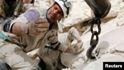 Một nhân viên cứu nạn tại địa điểm bị không kích ở Aleppo, 25/4/14
