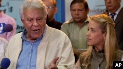 Spain's former prime minister Felipe Gonzalez, speaks to reporters as Lilian Tintori wife of jailed opposition leader Leopoldo Lopez looks at him during a press conference at the headquarters of Movement of Democratic Unity (MUD) opposition coalition in Caracas, Venezuela, June 8, 2015.