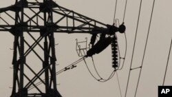 In this Saturday, Feb. 8, 2014 photo, linemen are silhouetted as they work to restore electrical power, at an electric pole in Krang Thnong at the outskirt of Phnom Penh, Cambodia. (AP Photo/Heng Sinith)