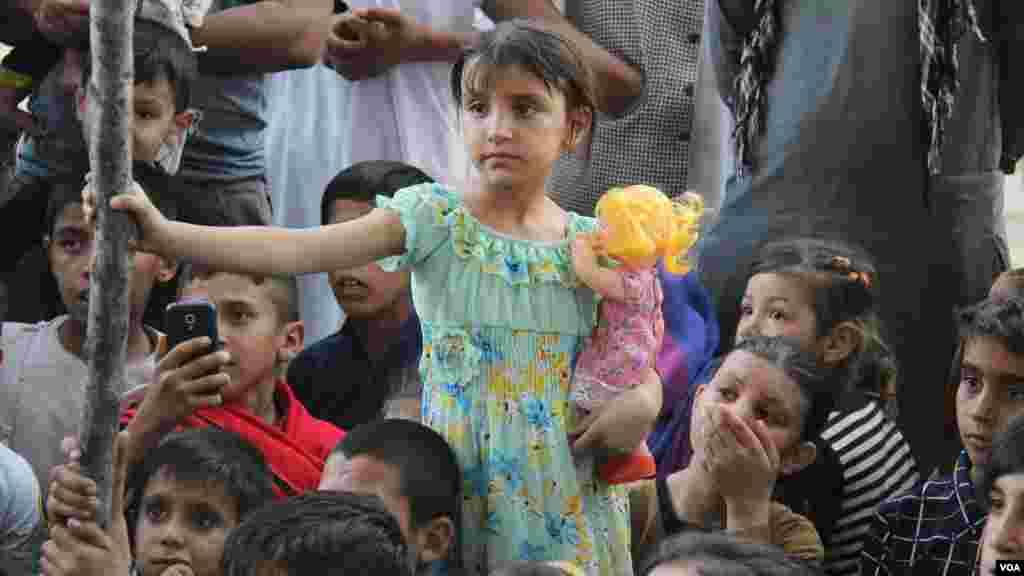 دختر افغان که با دقت به تماشای نمایش سرکس می پردازد