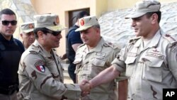 In this picture provided by the office of the Egyptian Presidency, Egyptian President Abdel Fattah el-Sisi, second left, greets members of the Egyptian armed forces in Northern Sinai, Egypt, July 4, 2015.