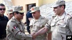 """Presiden Abdel-Fattah el-Sisi (kiri) menyalami anggota pasukan Mesir yang bertugas di Sinai (foto: dok). Militer Mesir menuduh aktivis HAM Hossam Bahgat """"membahayakan keamanan nasional""""."""