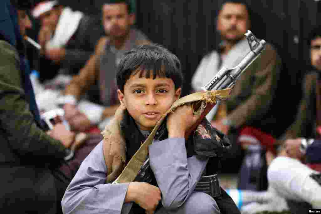 A boy holds a rifle as he attends a rally of Houthi movement supporters to mark the Ashura in Sana'a, Yemen.