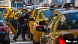 FILE - A woman exits a taxi on Third Avenue in heavy traffic caused in New York, Sept. 24, 2013.