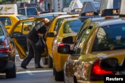 FILE - A woman exits a taxi on Third Avenue in heavy traffic. Carpooling can help reduce one's carbon footprint.