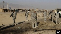 US soldiers inspect the site of suicide attack in Kandahar, Afghanistan, Saturday, Dec. 18, 2010.