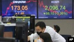 南韓首爾韓亞銀行外匯交易處的貨幣交易員戴著口罩監看行情。(2020年2月24日)