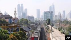 Kereta api bergerak di tengah asap puolusi kota Jakarta, Kamis, 16 September 2021. (AP Photo/Tatan Syuflana) Pemerintah memperpanjang PPKM per level di Jawa dan Bali.