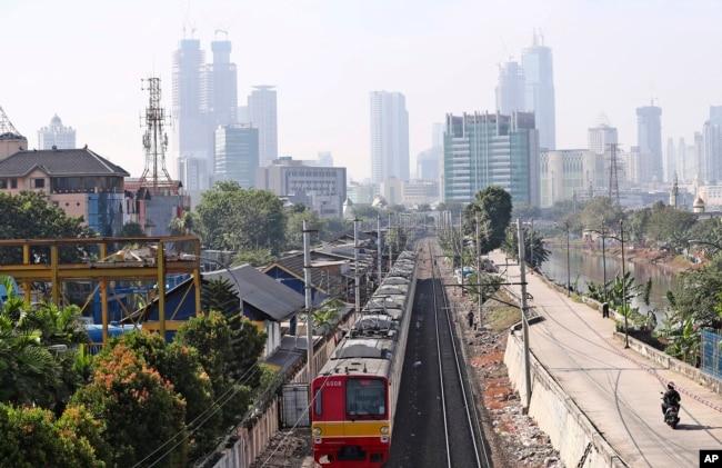 Sebuah kereta api bergerak di jalurnya di tengah polusi kota Jakarta, Kamis, 16 September 2021.