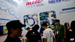 FILE - Visitors are seen at a social network company booth at the 2016 Global Mobile Internet Conference (GMIC) in Beijing, China, April 28, 2016. Last year, China passed a cybersecurity law that foreign companies say might isolate Chinese industries.