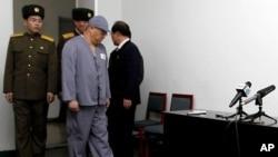 裴俊浩在看押下抵达平壤友谊医院的记者会现场。(2014年1月20日)