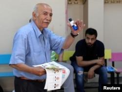 Un hombre gesticula mientras lleva una papeleta en una mesa electoral ubicada en una escuela durante las elecciones en Estambul, Turquía, el 24 de junio de 2018.