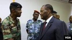 Presiden Alassane Ouattara (kanan) berjabat tangan dengan Jenderal Philippe Mangou, di Hotel Golf, Abidjan (12/4).