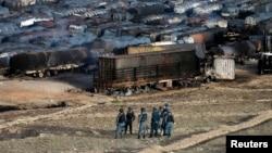 阿富汗警察站在油罐車遭焚燒後的現場