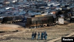 Afghan policemen stand at the site of burning fuel trucks after an overnight attack by the Taliban on the outskirts of Kabul, July 5, 2014.