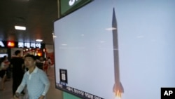 A man passes by a TV news program with file footage of a North Korean rocket launch at the Seoul Railway Station in Seoul, South Korea, Wednesday, Aug. 3, 2016. North Korean missile launches raise tensions with its neighbors in the area.