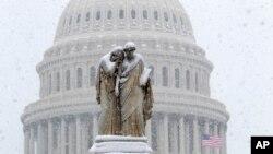 눈이 쌓인 워싱턴 D.C.의 평화 기념비 너머로 연방 의사당이 보인다.