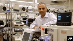 In this Aug. 10, 2015, photo, Dr. Akhilesh Pandey, a researcher at Johns Hopkins University, poses alongside a mass spectrometer in his laboratory in Baltimore.