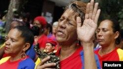 Seorang warga Venezuela memegang boneka Presiden Hugo Chavez dalam doa massal untuk kesehatan Chavez di Caracas. (Foto: Reuters)