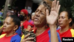 A woman holds a figurine of Venezuelan President Hugo Chavez, as she attends a mass to pray for Chavez's health in Caracas December 11, 2012.