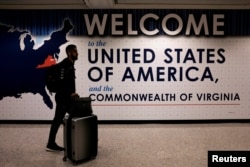 FILE - An international passenger arrives at Washington Dulles International Airport in Virginia.