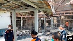Polisi memeriksa sel-sel yang hangus terbakar di Penjara Tangerang, Rabu, 8 September 2021.(Kementerian Hukum dan Hak Asasi Manusia Indonesia via AP)
