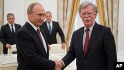 Russian President Vladimir Putin, left, shakes hands with U.S. National security adviser John Bolton during their meeting in the Kremlin in Moscow, Russia, June 27, 2018.