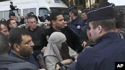 An unidentified veiled woman is taken away by plain clothed and uniformed police officers in Paris, Monday, April 11, 2011