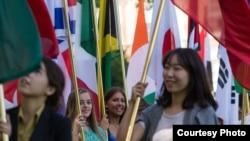 國際學生舉著代表他們自己國家的國旗參加美國密蘇里州立大學畢業典禮。