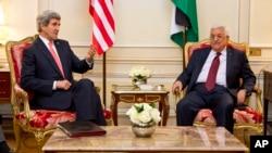 Menteri Luar Negeri John Kerry (kiri) dalam pertemuan dengan Presiden Palestina Mahmoud Abbas di Paris (19/2).