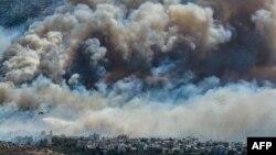 17일 그리스 아테네 외곽에서 대규모 산불이 발행해 도심이 짙은 연기로 뒤덮여있다.