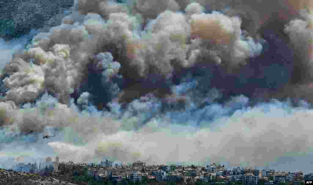 An airplane of firefighters flies over smoke over Athens, Greece, as firemen were battling a brush fire in northeastern Athens and another wildfire in the southern Pelopponese peninsula that led to residents from five villages evacuating.