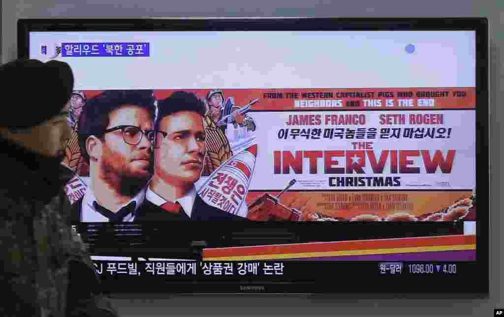 """Seorang tentara Korea Selatan melewati iklan film """"The Interview"""" dari Sony Pictures di stasiun kereta Seoul (22/12). (AP/Ahn Young-joon)"""