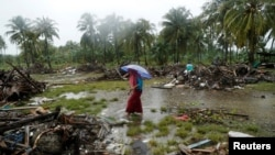 A woman holding an umbrella walks in the rain among debris after a tsunami, in Sumur, Banten province, Indonesia, Dec. 26, 2018.