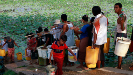 In this photo taken on April 21, 2012, local residents line up to fetch drinking water from a lake in Rangoon, Burma. (AP Photo)