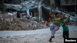 Anak-anak Palestina bermain di dekat reruntuhan bangunan di Beit Hanoun, Jalur Gaza yang hancur akibat serangan Israel tahun lalu (foto: dok).