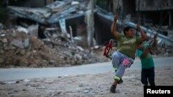 Anak-anak Palestina bermain di antara reruntuhan bangunan di Beit Hanoun, Jalur Gaza (foto: dok). Laporan PBB mengatakan sekurangnya 557 anak Palestina tewas dalam konflik Gaza tahun lalu.
