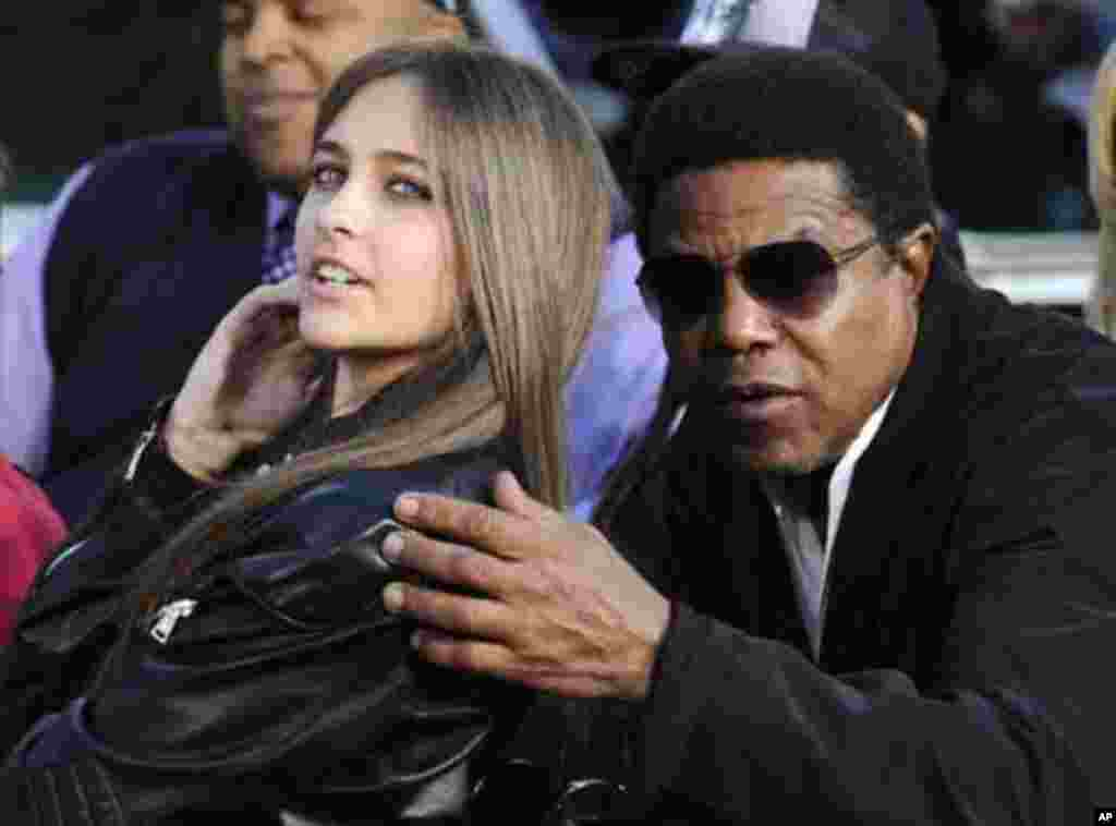 Michael Jackson's daughter Paris (L) and brother Tito Jackson share a moment at a ceremony where the singer is immortalized with hand and foot imprints in cement in the courtyard of Hollywood's Grauman's Chinese Theatre in Los Angeles January 26, 2012. RE