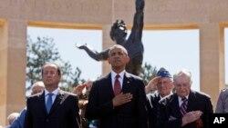 ປະທານາທິບໍດີຝຣັ່ງ ທ່ານ Francois Hollande (ຊ້າຍ) ແລະ ປະທານາທິບໍດີສະຫະລັດ ທ່ານບາຣັກ ໂອບາມາ (ກາງ) ຢືນກັບພວກນັກລົບເກົ່າ ທີ່ສຸສານອາເມຣິກັນ ຢູ່ເມືອງ Normandy ໃນວັນຄົບຮອບ 70 ປີ ຂອງການຍົກພົນຂຶ້ນບົກ ຫລື D-Day (6 ມິຖຸນາ 2014)